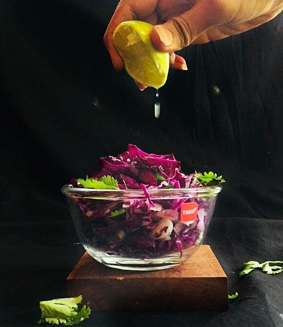 Healthy purple salad representing purple cabbage/lettuce, onions, squeeze of lemon, parsley's.